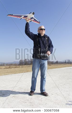 Happy man launching a remote controlled airplane into the air