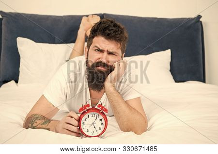 Hipster Bearded Man Lay In Bed With Alarm Clock. Time To Wake Up. Why You Should Wake Up Early Every