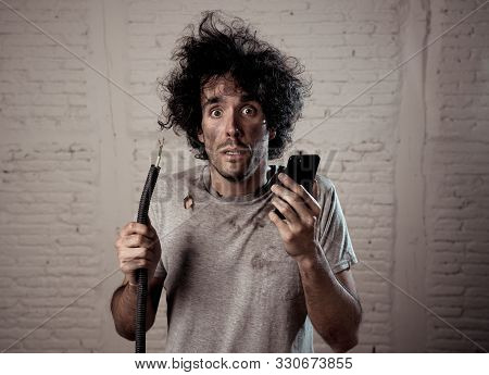 Portrait Of Young Man Holding Electrical Cable After Domestic Accident With Dirty Burnt Funny Face E