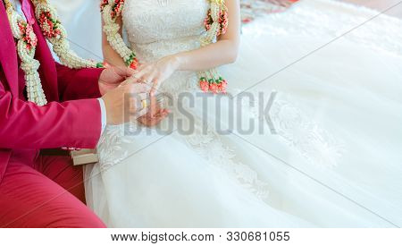 Groom Put Wedding Diamond Ring On Bride Finger For Proposal On Wedding Ceremony Day. Bride And Groom