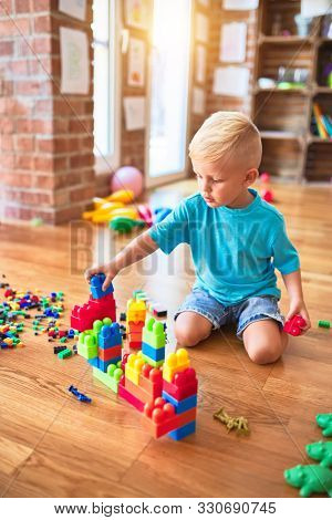 Young caucasian kid playing at kindergarten with toys blocks. Preschooler boy happy at playroom building a tower