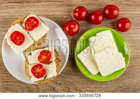 Two Sandwiches With Soft Cheese And Tomato Cherry In White Saucer, Tomatoes, Slices Of Cheese In Gre