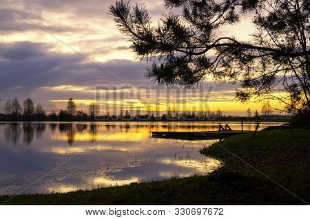 Tranquil Lake Reflecting A Vivid Orange Sunset With Silhouetted Trees And A Landing Jetty For Boats
