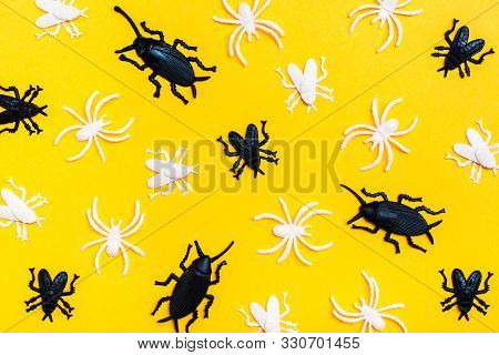 Black And White Plastic Flies And Beetles Lie Randomly On A Yellow Cardboard Background. Ready Backg