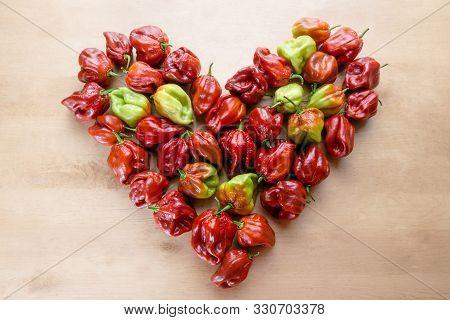 Red Hot Chilli Pepper Scotch Bonnet Caribbean Antillais On Wooden Background Colourful In Heart Shap