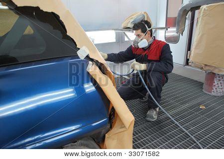 Young mechanic varnishing a car