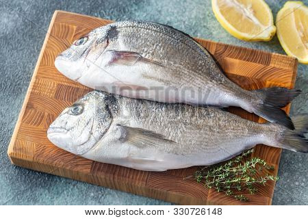 Fresh Dorada With Thyme And Halved Lemon On The Wooden Board
