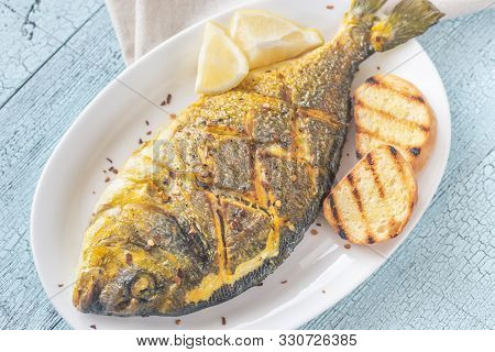 Fried Saffron Sea Bream With Toasted Bread Close Up