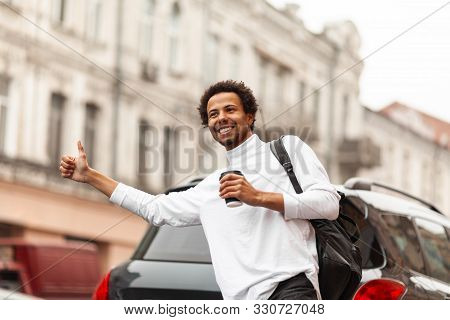 Young Attractive African Man Hailing Cab (taxi) On City Street, Raises His Hand.