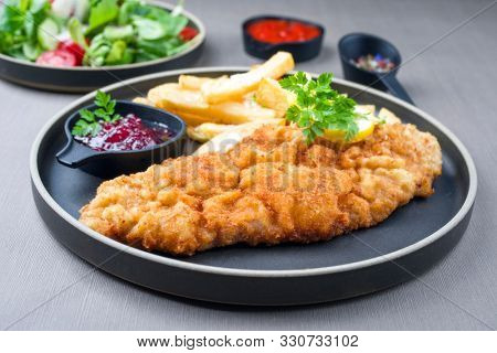 Fried Wiener schnitzel from veal topside with French fries and lettuce as closeup modern design plate
