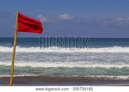 Red Warning Flag Flapping In The Wind On Beach At Stormy Weather.