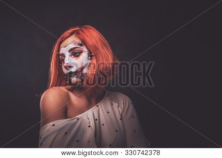 Pretty Young Woman With Scary Dead Doll Makeup Is Posing For Photographer At Dark Photo Studio.