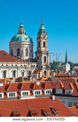 St. Nicolas Church And And Red Roofs Of Prague On A Bright Day With Blue Sky, Bird View. Prague, Cap