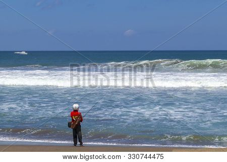 Fisherman In Helmet Looking Like Astronaut Standing And Fishing On The Beach Next To The Sea