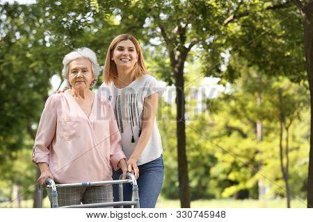 Caretaker Helping Elderly Woman With Walking Frame Outdoors
