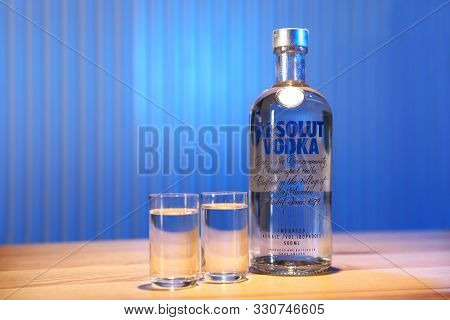 Mykolaiv, Ukraine - September 23, 2019: Absolut Vodka And Shot Glasses On Wooden Bar Counter. Space