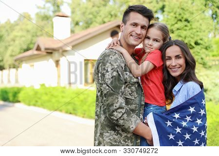 Man In Military Uniform And His Family With American Flag Outdoors
