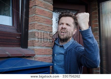 Angry Upset Young Male Neighbor With Fist In Air, Open Mouth Yelling.