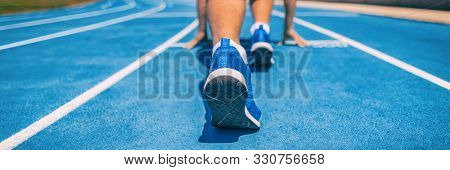 Sprinter fit man waiting for start of race on running tracks at outdoor stadium. Sport and fitness runner athlete on blue run track starting line with running shoes. Banner panorama.