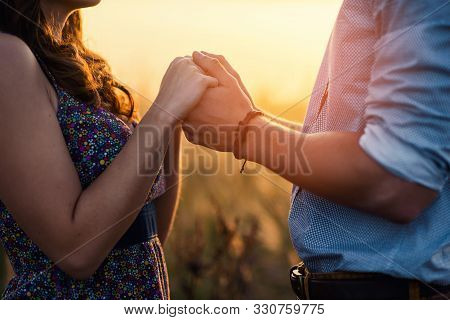 Holding Hands Loving Couple Stands In The Middle Of The Wheat Field At Sunrise. A Young Couple In Lo