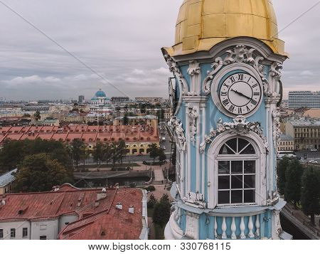 Photo of old blue belfry with clocks on each side of the tower. The bell tower is crowned by a golden dome. On the background white cathedral. Aerial city view, red roofs. Saint Petersburg, Russia. poster