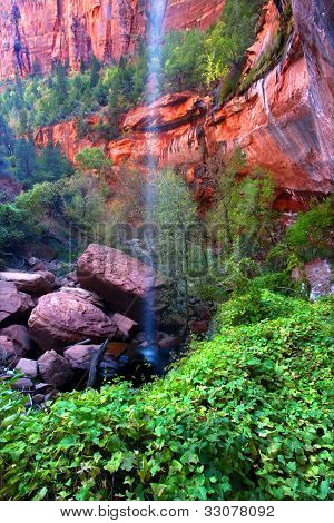 Waterfall flows into the Lower Emerald Pools of Zion National Park in Utah. poster
