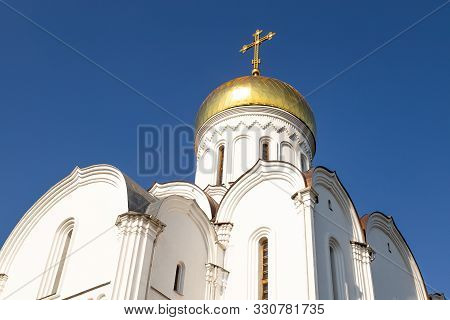 Bottom View Of White Eastern Church With Sunlit Gilt Dome Against Clear Blue Sky