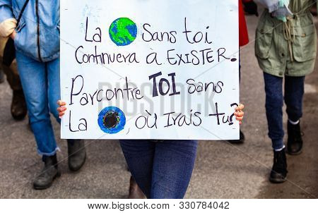 Environmentalists March For Climate Change, Holding A French Poster Saying The Earth Will Continue T