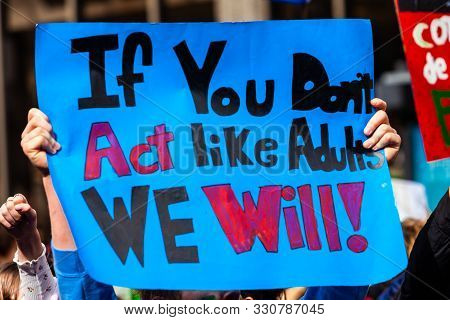 A Colorful Poster Is Seen Close-up, Held In The Hands Of An Environmentalist, Saying If You Dont Act