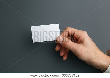 Male Hand Holding A Blank Business Card On Grey Background For Text Or Design. Blank Credit Card Tem