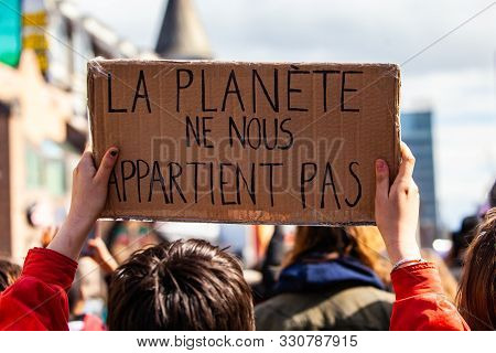 A Close Up View Of An Environmentalist Holding A Cardboard Sign With The French Words The Planet Doe