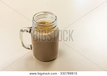 A close up shot of a healthy smoothie. Mixed and prepared brown bsissa served in a glass tankard. Isolated against a clean white background. poster