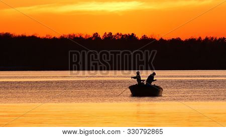 Silhouette Of Father And Son Fishing On A Beautiful Lake At Sunset In Northern Minnesota.