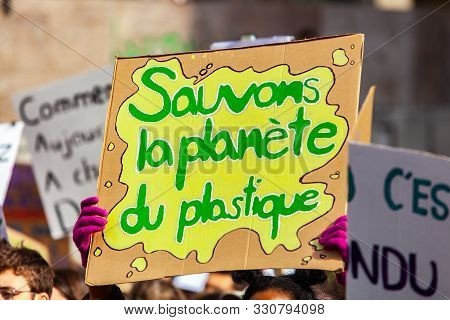 A Close Up Shot Of A Homemade French Sign, Saying Save The Planet From Plastic, Held By A Protestor