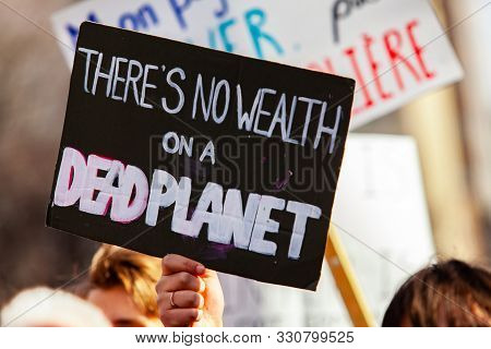 A Closeup View Of A Homemade Banner, Reading Theres No Wealth On A Dead Planet, As A Crowd Of Ecolog