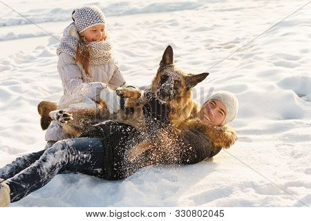 Joyful Teens Spend Time Together With Lovely Pet German Shepherd Dog On A Walk In The Winter Park On