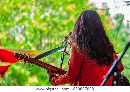 A Female Musician Is Viewed From Behind As She Sings And Plays The Guitar During A Live Music Gig In