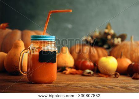 Pumpkins Juice In Bottles With Pumpkins. Cup Of Pumpkin Juice, Pumpkins On Wooden Table. Cup Of Pump