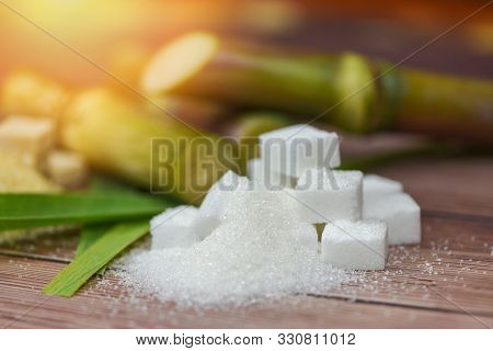 White Sugar Cubes And Sugar Cane On Wooden Table And Sunlight Nature Background