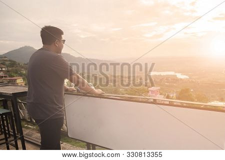 Asian Man Is Standing On The Balcony To See The Beautiful Sunset At Petchabun Provice , Thailand.