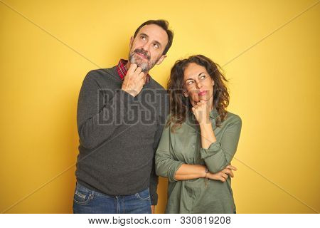 Beautiful middle age couple over isolated yellow background with hand on chin thinking about question, pensive expression. Smiling with thoughtful face. Doubt concept.