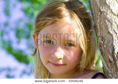6 Year Old Girl Smiling At The Park Leaning Against Tree