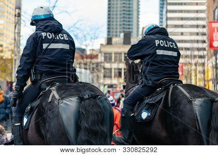 Two Horseback Police Officers Are Seen From Behind, On Duty As Environmentalists Rally In A Town Cen