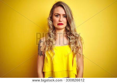 Young attactive woman wearing t-shirt standing over yellow isolated background depressed and worry for distress, crying angry and afraid. Sad expression.