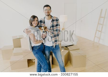 Happy Woman And Man Tenants Or Renters Of Flat Pose In Own House, Cuddle And Pose With Little Dog, H