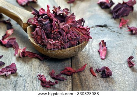 Dry Hibiscus In A Wooden Spoon. Dried Hibiscus Petals On A Wooden Table. Hibiscus Tea.  Vitamin Tea