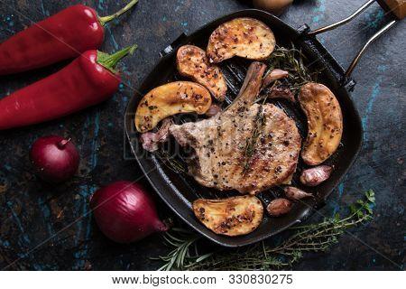 Spicy pork loin chop steak served over roasted potato