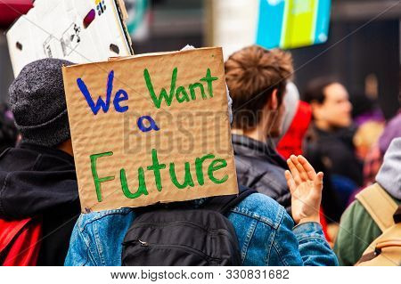A Cardboard Sign Is Viewed Close-up Saying We Want A Future As A Crowd Of Environmental Campaigners