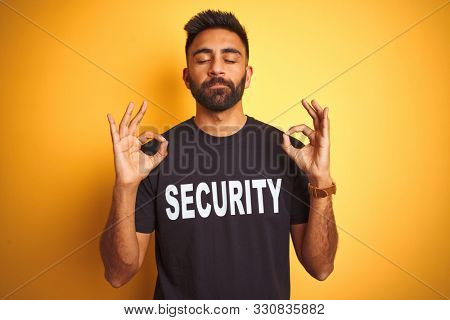 Arab indian hispanic safeguard man wearing security uniform over isolated yellow background relax and smiling with eyes closed doing meditation gesture with fingers. Yoga concept.