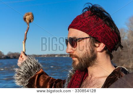 A Close-up Side Profile View Of A Shaman Guy Wearing Sunglasses And Red Bandanna, Holding A Sacred D
